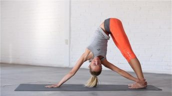 Revolved Downward Dog rotates the spine and stretches the calves and hamstrings.